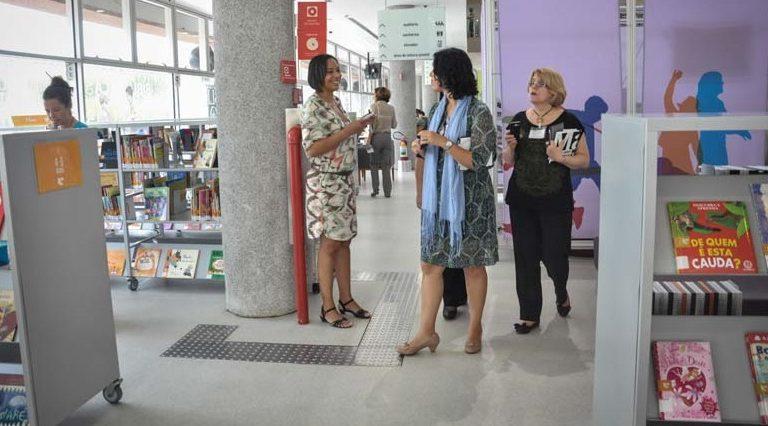 Três mulheres estão em pé no corredor de uma biblioteca.