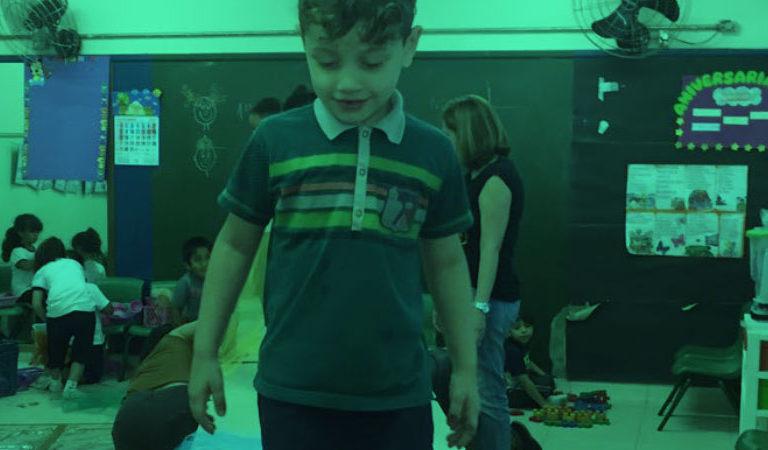 Um garoto ao centro, olha para baixo, numa sala de aula com outras crianças que brincam. A educadora está ao fundo.
