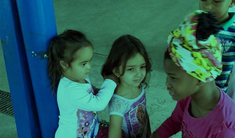 Três meninas estão juntas em um pátio. Uma delas é branca, tem deficiência. Ela mexe no cabelo solto de uma menina branca que está sentada na sua frente. Ao lado, uma menina negra também está sentada e tem um tecido em seus cabelos. Dois meninos aparecem ao lado, com parte de seus rostos aparecendo.