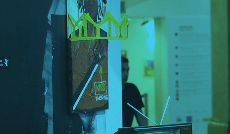 Imagem da exposição Basquiat, com dois objetos táteis: a coroa e o braço articulado. Perto da coroa, há uma pintura e uma televisão antiga. Uma pessoa aparece na foto, entrando por uma porta.