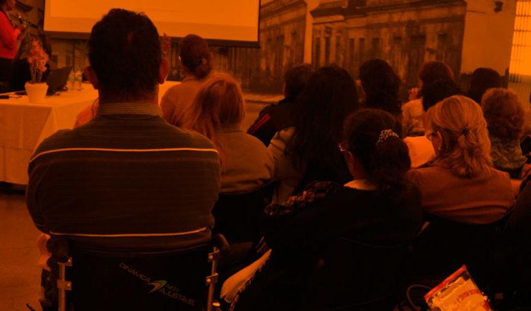 Plateia composta por homens e mulheres vistos de costas