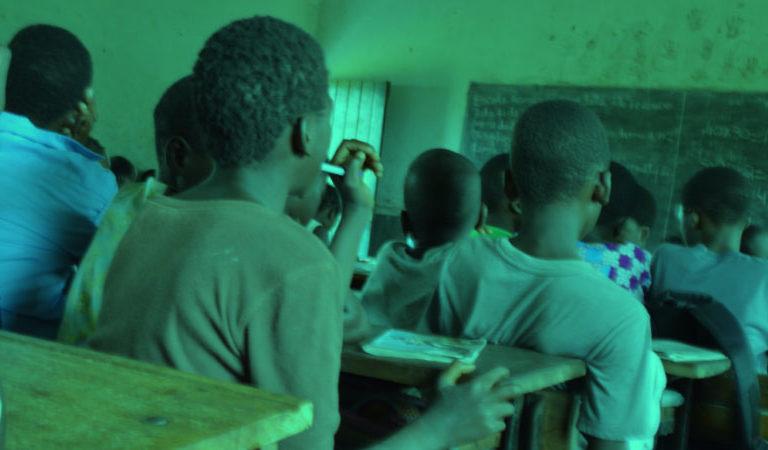 Meninos de costas estão em uma sala de aula de uma escola em Mocambique. Ao fundo, se vê a lousa.