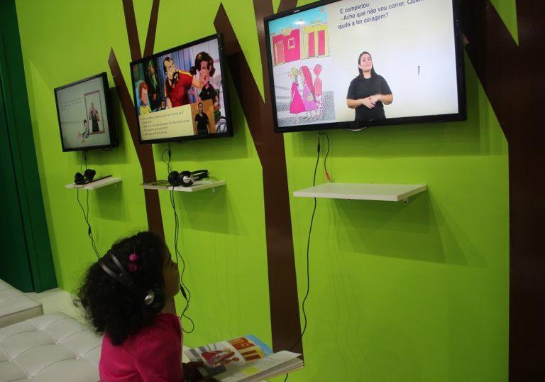 Uma menina está sentada e segura um livro em seu colo. Ela usa fones de ouvido e olha para uma tela onde é exibido um livro audiovisual em múltiplos formatos acessíveis