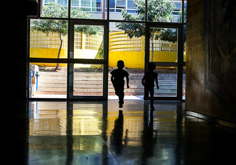 Duas crianças correm em direção ao pátio de uma escola.