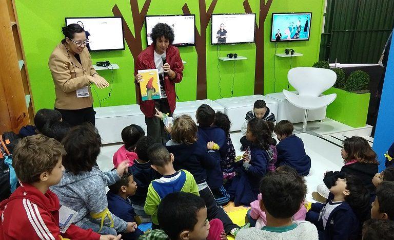 Grupo de crianças reunidas no estande da Bienal assistem à apresentação de uma mulher que veste casaco vermelho e está com um livro em mãos. Ao lado dela, está uma intérprete de Libras.