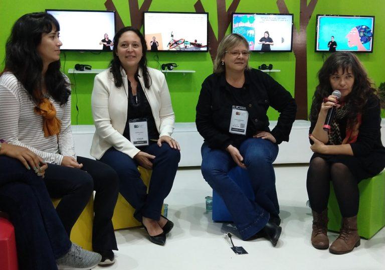 Quatro mulheres estão sentadas e participam de debate no estande da Bienal. Ao fundo, três monitores de TV exibem livros editados em múltiplos formatos acessíveis
