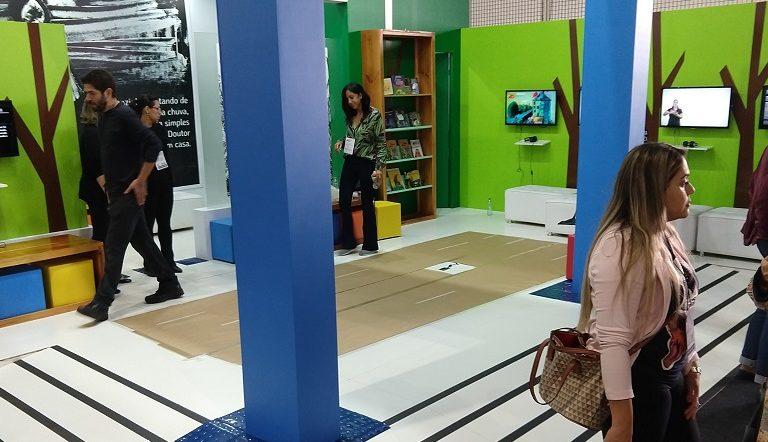 Visão do estande de livros em múltiplos formatos acessíveis na Bienal 2018. Há bancos coloridos e cadeiras brancas. Uma estante com livros e monitores de TV afixados em paredes verdes.