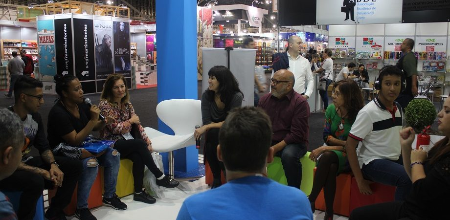 Homens e mulheres estão sentados e participam de um debate no estande da Bienal. Uma mulher à esquerda está com microfone em mãos. Ao fundo, é possível ver corredores e outros visitantes da Bienal.