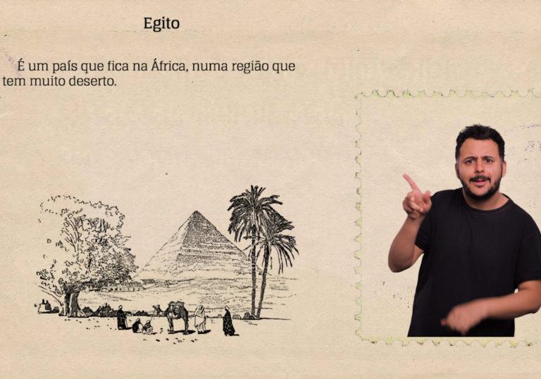 """Imagem de uma cena do livro audiovisual acessível na qual aparecem o intérprete de Libras e o texto """"É um país que fica na África, numa região que tem muito deserto"""". Uma ilustração apresenta uma cena do Egito, com pirâmides e o topo das árvores."""