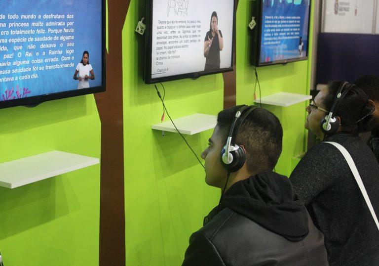 Um jovem e uma mulher estão sentados e usam fones de ouvido. Em frente a eles, duas telas exibem livros audiovisuais em múltiplos formatos acessíveis