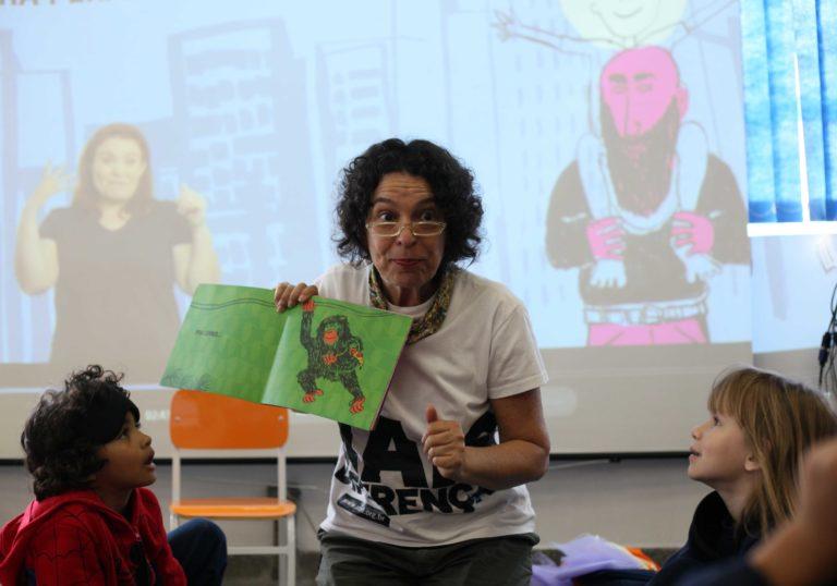 A mediadora Suia Legaspe segura um livro aberto e mostra a algumas crianças que estão sentadas em frente a ela