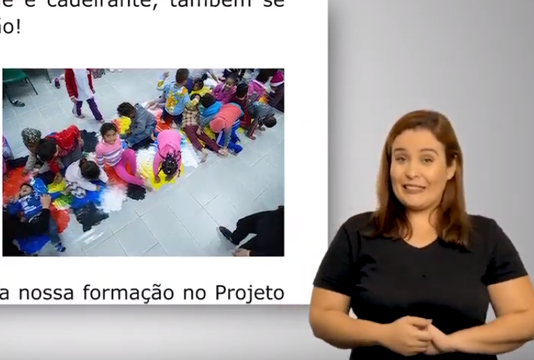 À direita, está a intérprete de Libras. Ela tem cabelos lisos e veste camiseta preta. À esquerda, há, duas fotos com dezenas de crianças brincando com tintas coloridas, deitadas no chão.