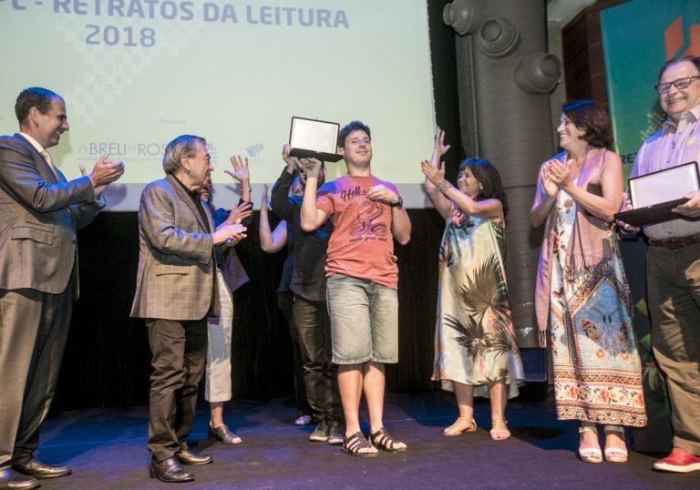 Na foto, Mario Paulo segura a placa de premiação recebida pela Mais Diferenças. Ao lado esquerdo, está o cartunista Mauricio de Souza, que veste terno. Ao lado direito, está Carla Mauch, que usa um vestido colorido.