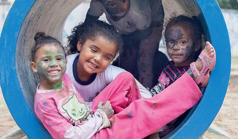 Quatro crianças estão dentro de um túnel de parquinho. Três delas estão com os rostos pintados.