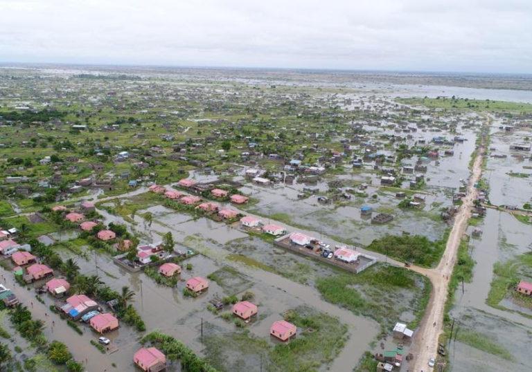 A imagem mostra uma cidade alagada vista de cima. Várias casas e áreas verdes estão envoltas por água em um território amplo.