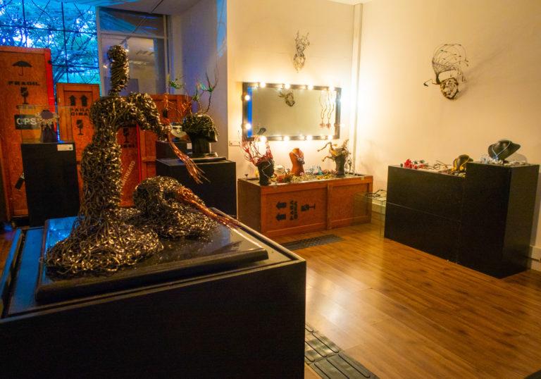 Imagem mostra uma escultura de alumínio e, ao fundo, um espelho iluminado que representa a seção camarim da exposição