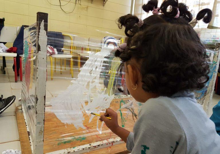 Uma menina de costas pinta sobre uma superfície de plástico. Ela usa tinta branca