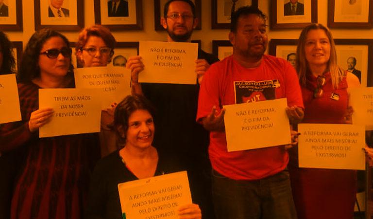 A foto mostra mulheres e homens seguram cartazes com frases como Não é reforma! É o fim da previdência e A reforma vai gerar ainda mais miséria. Pelo direito de existirmos!