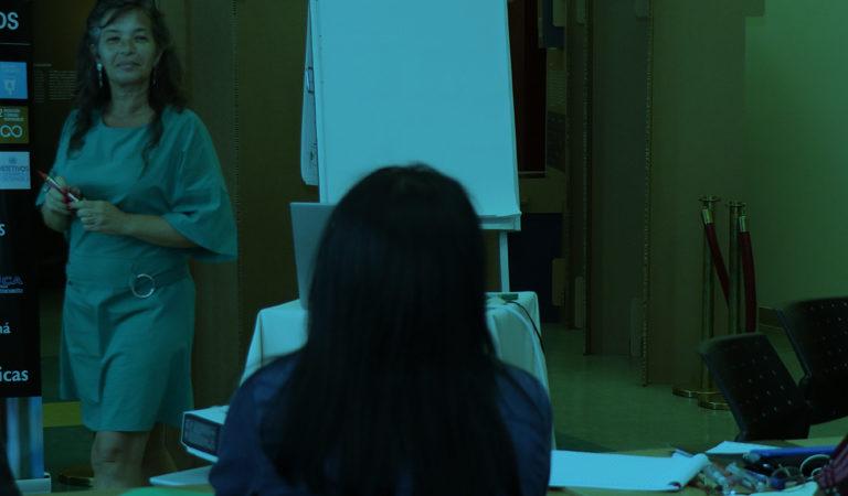 A foto mostra Carla Mauch em pé, de vestido verde, sorrindo para homens e mulheres sentados de costas para a câmera. Atrás de Carla, é possível ver o banner do evento com a frase Bibliotecas y ODS