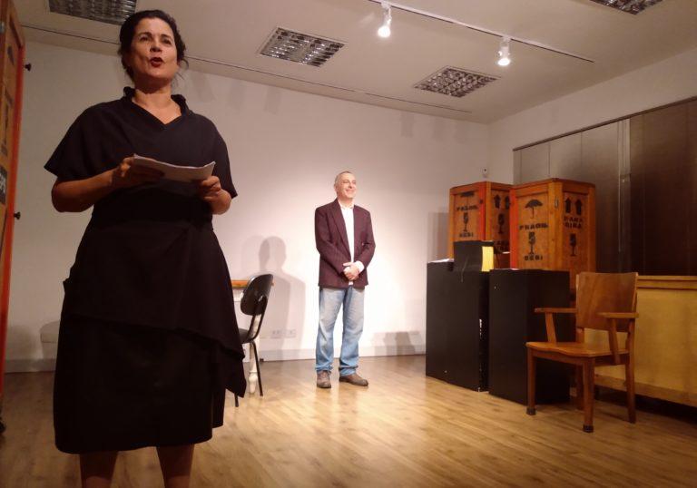 Dois atores em cena em uma sala com três grandes caixas de madeira ao fundo. À esquerda da imagem, a atriz segura uma folha de papel com as duas mãos e olha para a plateia. Ela veste roupa preta e está de costas para o ator que usa um paletó e está de pé no fundo da sala.