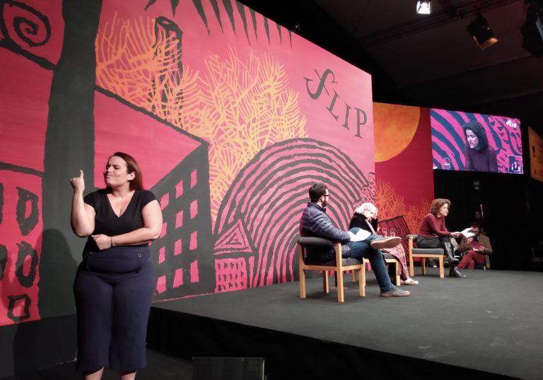 À esquerda da foto está a intérprete de Libras, que usa uma blusa preta. Ao fundo, podemos ver um homem e duas mulheres sentados.  Eles estão à frente de uma grande painel de cores vermelho, laranja e preto com desenhos e escrito Flip