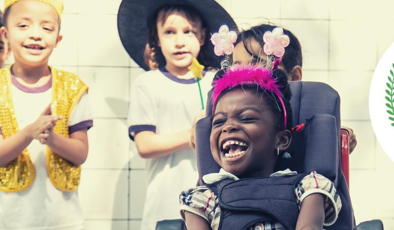 """Foto retangular na horizontal na qual crianças brincam fantasiadas com adereços como chapéus, tiaras e peças de roupas coloridas. Uma delas é uma menina cadeirante com um largo sorriso em primeiro plano. Ao fundo, alguns meninos sorriem e batem palmas. No canto direito, há uma bola branca com uma ilustração de coroa de loros verde e o logo do Zero Project. Ao centro da bola, lê-se em preto """"Award winner 2020""""; em português, """"vencedor do prêmio 2020"""""""