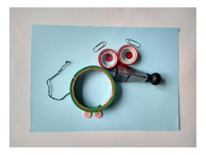 Desenho escultura de um rato. Seu corpo é feito de um rolo de fita adesiva grande, seus olhos de dois rolos menores, seu nariz de um pequeno ralador de queijo, suas sobrancelhas e seu rabo de clipes e suas patinhas de pequenos botões.