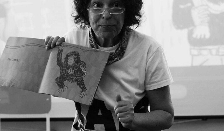 Descrição da imagem: Mulher segundando um livro que contém a ilustração de um macaco