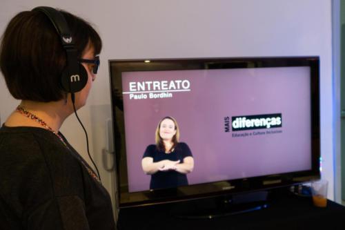 Visitantes assistem ao vídeo de introdução à exposição em formato acessível