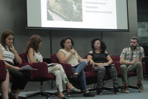 Professoras, coordenadoras do Projeto Brincar e um consultor estão no palco de um auditório. Uma das professoras segura um microfone.