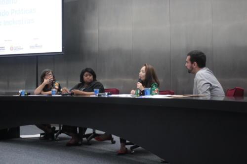 Representantes das organizações parceiras estão sentados atrás de uma mesa. Sandra Kahori, da Secretaria Municipal e Educação de São Paulo segura o microfone.