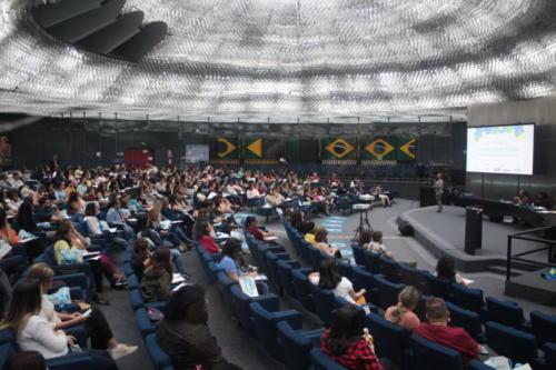 Há muitas pessoas sentadas na platéia do auditório do Memorial da Inclusão. No palco, a imagem mostra duas pessoas sentadas e uma intérprete de Libras