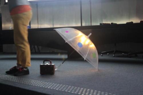A foto mostra uma parte do corpo de Thiago Franco. Suas pernas são vistas ao lado de uma pequena mala e um guarda-chuvas