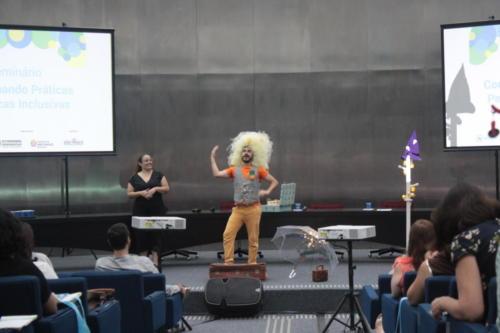 Thiago Franco está sobre o palco e veste um dos chapeus da história o Rei Careca. Ao lado, há uma intérprete de Libras.