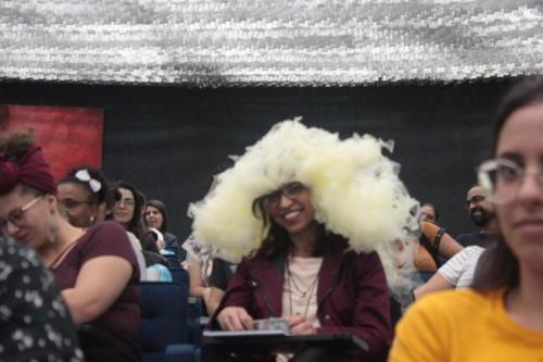 Uma professora na plateia veste uma espuma na cabeça durante atividade lúdica parte da mediação de leitura.