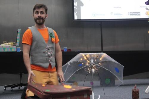 Thiago Franco está sobre o palco, ajoelhado em frente a uma maleta. Ao seu lado há um guarda-chuva iluminado