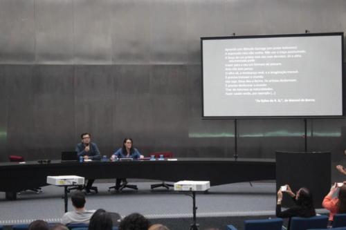 Duas pessoas estão sentadas atrás de uma mesa no palco do auditório. Ao lado, há um telão com uma apresentação.