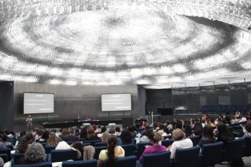 Vista de fundo do auditório do Memorial da Inclusão. Jefferson Fernandes Alves e Karyne Dias Coutinho estão no palco, onde também há uma intérprete de Libras.