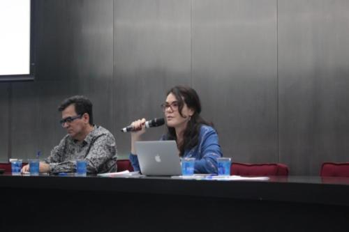 Jefferson Fernandes Alves e Karyne Dias Coutinho estão no palco, sentados atrás de uma mesa.