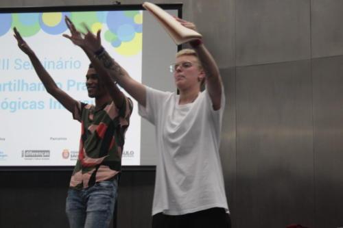 Dois integrantes do Slam do Corpo estão com os braços para o alto.